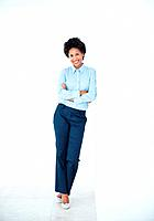 Full length of smiling African American business woman leaning against wall