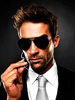 Closeup of secret service agent talking on his earphones against black background