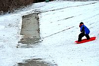 sledding near the sidewalk