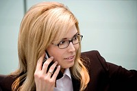 blond young business woman phoning by mobile