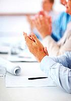 Cropped image of business people clapping hands during meeting at office