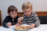 two little boys sitting at the kitchen table contending about Christmas cookies on a plate