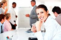 Happy businesswoman sitting in office with colleagues working in background