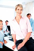 Portrait of a smiling young businesswoman sitting on the desk and her colleagues working behind at office