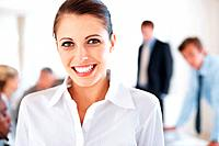 Portrait of a happy young businesswoman with her colleagues working behind at office