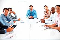 Portrait of business team sitting at conference table and looking at you