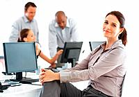 Portrait of beautiful business woman working in office with colleagues in background