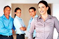 Portrait of pretty female executive standing in front of her team and smiling
