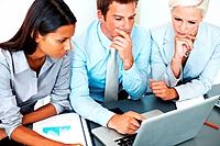 Confident businessman sitting with his colleagues and working on laptop _ Teamwork
