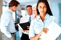 Successful youg businesswoman standing with a paper while group discussing in background