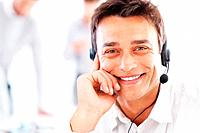 Closeup of handsome business man wearing headset with colleagues in background