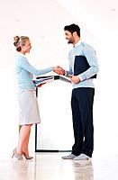 Full length of business man and woman shaking hands after the deal is confirmed