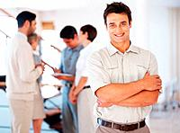 Confident business man smiling with colleagues discussing in background