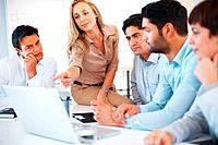 Cute business woman sitting on table and pointing at laptop during meeting