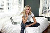 Smiling Young Woman Sitting on Bed with Laptop