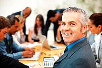 Happy male executive while colleagues discussing in a meeting