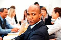 African American business man with team in background during meeting