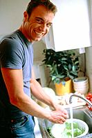 Young Man Washing Salad in Kitchen