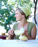 Woman Cutting a Melon at Table