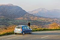 woman standing roadsides behind her car and enjoying the , Ireland, Beara Peninsula