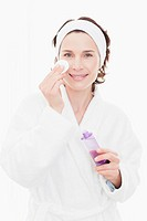 Woman in bathrobe cleansing her face