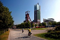 two bikers in Nordsternpark with headgear and tower NT 2, Germany, North Rhine_Westphalia, Ruhr Area, Gelsenkirchen