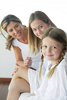 Girl sitting with mother and grandmother, portrait