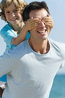 Boy covering father´s eyes with hands