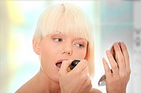 A beautiful young woman applying her make_up