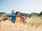 Couple sitting back to back in field after exercise