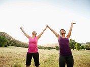 Athletic women standing in field with arms raised