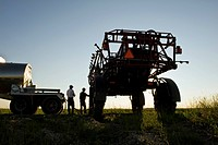 Two farmers load a high clearance sprayer with chemical fungicide and water from a nurse truck, near Dugald, Manitoba