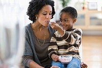 African American boy feeding mother ice cream