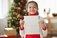 Hispanic girl writing Christmas letter to Santa
