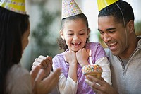 Mother and father giving daughter birthday cupcake