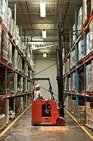 Hispanic worker operating forklift in warehouse