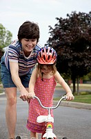 Mother Helping Daughter Ride Tricycle, Markham, Ontario
