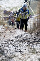 Cyclist carrying his bike up hill in a Cyclocross race, Toronto Ontario