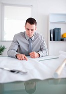 Close up of architect sitting behind a table and working on a construction plan