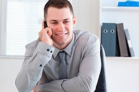 Smiling businessman using his cellphone