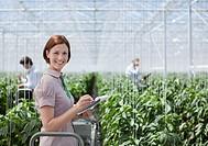 Woman writing on clipboard in greenhouse