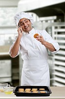 Chef talking on a mobile phone holding a cookie