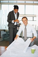 Business people examining blueprints in office