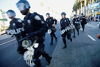 A group of riot police move into position near the Loews Santa Monica Beach Hotel in Santa Monica, California. Police are out in force during a round ...
