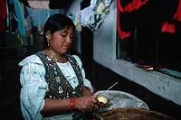 Mrs. Cushcagua peels potatoes while standing beneath clotheslines covered with drying laundry. Otavalo, Imbabura, Ecuador.