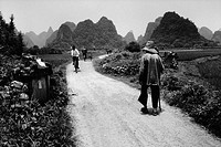 Bicyclists and pedestrians travel a dirt road winding through limestone hills in Gaotian Township, China.