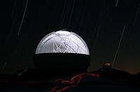 In a time_lapse photograph, the interior of the W.M. Keck Observatory is revealed through an open, rotating shutter.