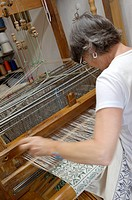 A female professional weaver operating an old loom making a fabric with traditional design carpet at Arteler workshop  Mezzano di Primiero, Italy