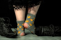 Feet of a girl in torn stockings and old shoes