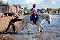 Female lead a horse to swim